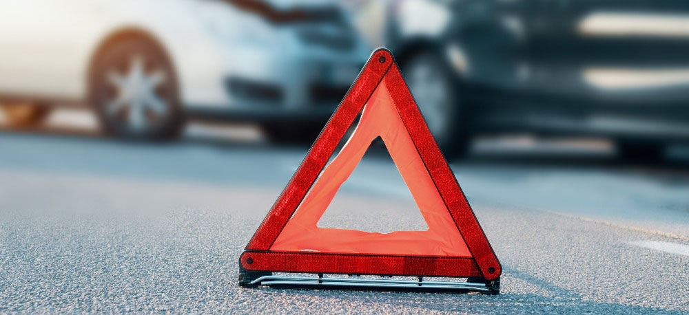 Orange caution sign near cars after an accident