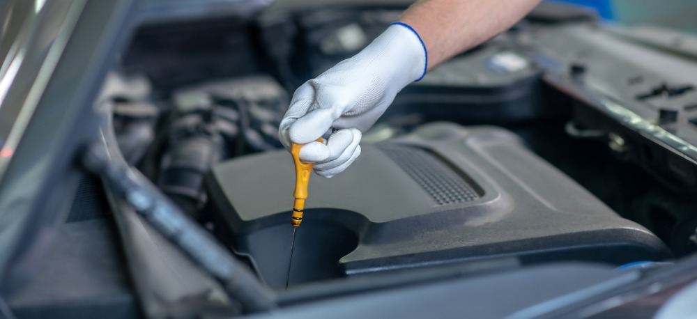 Man changing oil as part of routine car maintenance